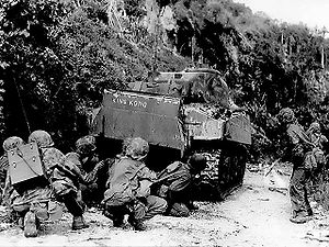 1st Battalion, 23rd Marines - Marines take cover behind a M4 Sherman tank while cleaning out the northern north end of the island of Saipan. July 8, 1944