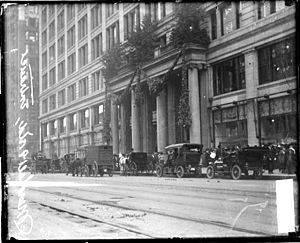 Marshall Field and Company Building - Entrance with Holiday decorations and automobiles parked along State Street, c.1910s