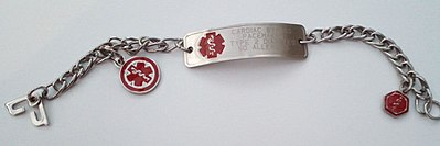 A metal bracelet, engraved with a short list of important medical information, and decorated with a red symbol representing medicine