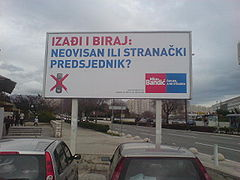 Pro-Bandić billboard in parking lot, with blue and red letters on white background