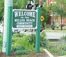 "A large sign reading ""Welcome to the Miller Beach Community, Gary, Indiana,"" next to a railroad crossing on a street with cars passing."