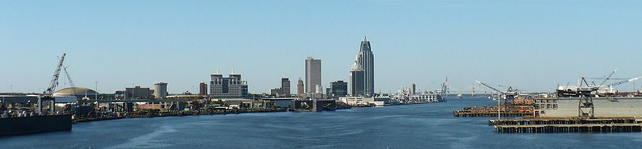 Panoramic view of a city's skyline; in the foreground, a large river and port facilities are present. In the distance, there is a city skyline with several skyscrapers of varying heights.