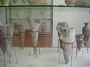 Steatite rhyta in foreground, clay on shelf behind.