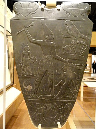 Hathor - Replica of the Narmer Palette, c. 31st century BC. The face of a woman with the horns and ears of a cow, representing Hathor or Bat, appears twice at the top of the palette and in a row on the belt of the king.