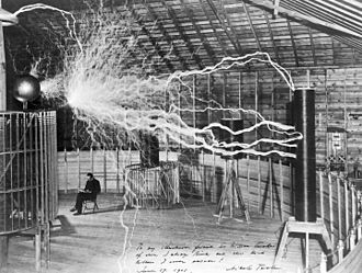 "Science and technology in the United States - Serbian-American inventor Nikola Tesla sitting in the Colorado Springs experimental station with his ""Magnifying transmitter"" generating millions of volts."