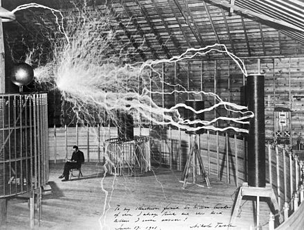 "A multiple exposure picture of Tesla sitting next to his ""magnifying transmitter"" generating millions of volts. The 7-metre (23 ft) long arcs were not part of the normal operation, but only produced for effect by rapidly cycling the power switch. Nikola Tesla, with his equipment Wellcome M0014782.jpg"
