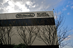 "A gray, nondescript building with ""Nintendo"" written on the top floor, and with trees in the foreground."