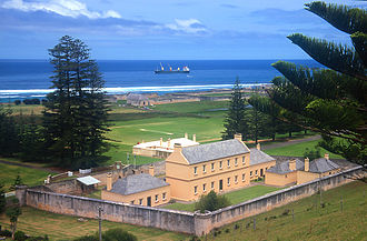 Kingston, Norfolk Island - Old Military Barracks, now Legislative Assembly Chambers, with Kingston Common in background