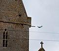 Normandy 10 Angoville-au-Plain Liberty Jump Team passing church (4824159497).jpg