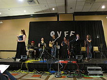Photograph of several people on stage in front of a black curtain bearing the letters O V F F.