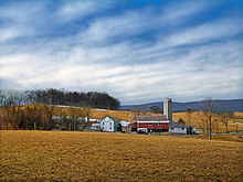 A grouping of farm buildings backdropped by a field, mountains, and the sky.