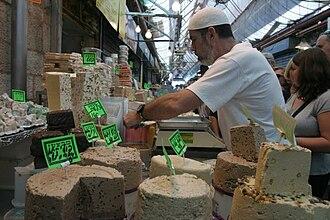 Mahane Yehuda Market - A halvah seller arranges his wares.