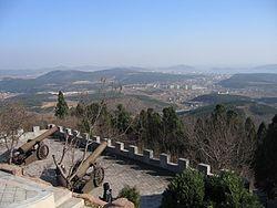 Vista do porto e da cidade de Lüshun em uma antiga fortificação japonesa