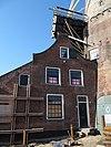 foto van Aan de voet van de molen muldershuis met tuitgevel, verdieping en roedenverdeling uit de bouwtijd. Naast het muldershuis aanbouw onder lessenaarsdak