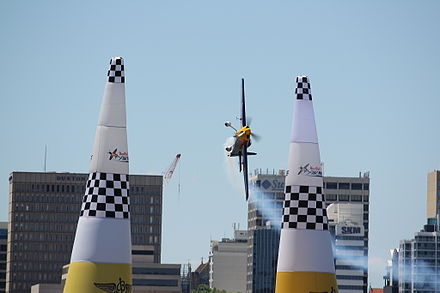 Péter Besenyei crossing between the start/finish pylons in Perth, 2008. The grey horizontal stripes in the pylons, e.g. below the checkered designs, are zippers. Red Bull Air Race Besenyei 1.JPG