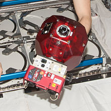 A SPHERES satellite equipped with add-on VERTIGO goggles.