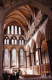A view into the north transept at Salisbury shows a harmonious arrangement of lancet arches rising in three tiers of various sizing and grouping. The details are enhanced by narrow attached shafts of dark-coloured Purbeck marble. The ribbed vault is of a simple form.