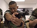 Seaman Caleb Shaw, a Cadet with the Navy Sea Cadet Corps, Kitsap Unit, looks down the site of a M9 Beretta.jpg