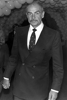 A black-and-white photo of actor Sean Connery, the setting consists of many balloons and two persons are located in the back.