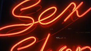 English: The glowing red neon sign spells out ...