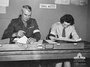 "Two soldiers, one male, one female, sit side by side doing paper work at a desk. They are wearing brassards and the sign behind them says: ""signal master""."