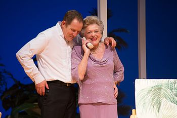 Todd McKenney with his arm over Nancye Hayes's shoulder as she takes a telephone call during a performance of the play Six Dance Lessons in Six Weeks