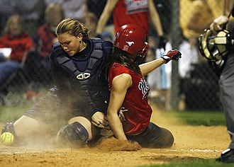 A collision at home base -- the player in red scores as the catcher has failed to secure the ball Softball home plate collision -1507299.jpg