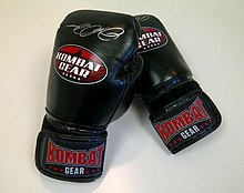 Photograph of a pair of black velcro sparring gloves, with Kombat Gear brand logos.