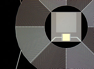 Netherlands Institute for Space Research - Optical photograph of a bolometer for SAFARI (detail); the shiny square is the superconducting TES thermometer, the large grey square is the Ta absorber. The ring-type structure is the SiN suspension, intended to produce a very weak coupling to the heat bath and thus a sensitive detector.