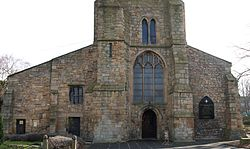 Stone building with two sloping wings, the left wider than the right; large stained glass window above door in the center, topped by lower part of tower