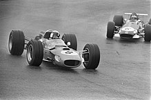 Black-and-white photograph of two Formula One cars driving on a wet track
