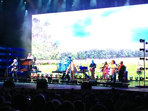 "The Rascals - The Rascals performing ""Groovin'"" during one of their 2013 Once Upon a Dream shows. The large video screen helped accentuate song themes and also showed interviews with members and re-enactments of the group's history. Left to right, Gene Cornish, Felix Cavaliere, Dino Danelli, Eddie Brigati, and various supporting players and singers."