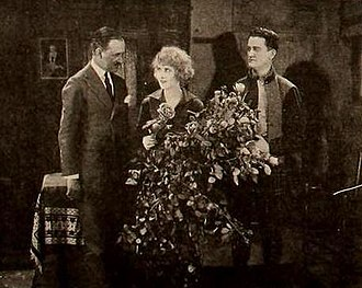 Charles Giblyn - Charles Giblyn (left) giving actress Pearl White a bouquet of rose on the set of The Tiger's Cub (1920)