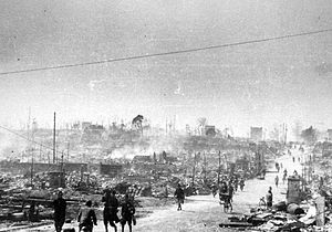 Black and white photo of people walking along a road passing through a large area of destroyed buildings