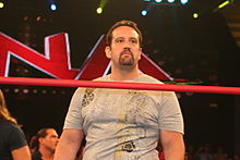Tommy Dreamer sur un ring portant un T-shirt blanc.