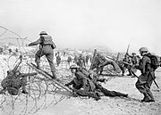 Troops of the 7th Battalion, the Suffolk Regiment, negotiate barbed-wire obstacles during training on the beach at Sandbanks near Poole, 22 March 1941. H8393