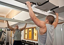 U.S. Air Force Senior Airman Brandon Stout performs pull-ups.jpg