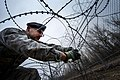 U.S. Air Force Tech. Sgt. Christopher Pike, the noncommissioned officer in charge of installation and physical security with the 376th Expeditionary Security Forces, connects concertina wire at the Transit 131212-F-VU439-178.jpg