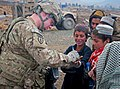 U.S. Army Pfc. Wayne Ellis, left, with the 3rd Platoon, Alpha Battery, 2nd Battalion, 377th Parachute Field Artillery Regiment, Task Force Spartan, draws on an Afghan boy's hand in a village near Forward 120203-A-ZU930-011.jpg