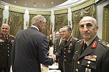 Mr Hagel, in a civilian suit, shakes hands with General Öztürk, in uniform.