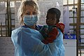 UK Emergency Medical Team Nurse Lynsey Phillips, pictured with a child who had just tested negative for diphtheria in Bangladesh (24855655927).jpg