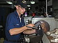 US Navy 060615-N-0000X-001 Machinery Repairman 2nd Class Evan Sams uses a milling machine to make a part for a submarine while in the machine repair shop aboard the submarine tender USS Frank Cable (AS 40).jpg