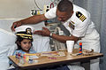 US Navy 061108-N-3750S-160 Cmdr. Brad Lee, commanding officer of USS San Antonio (LPD 17) places his cap on six year-old girl at Methodist Children's Hospital, making her an honorary ship's commander for a day.jpg