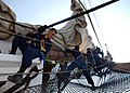 US Navy 070801-N-2385B-004 Working on USS Constitution's bowsprit, Seaman Apprentice Josh Bruner and other Sailors practice setting and furling the jib.jpg