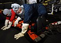 US Navy 070804-N-7981E-195 Hospital Corpsman 2nd Class Jessica Hall and members of her stretcher bearer team brace for shock while protecting a simulated casualty in the hangar bay of Nimitz-class aircraft carrier USS Abraham L.jpg