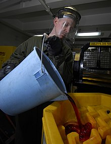 US Navy 090316-N-6597H-004 Boatswain's Mate 2nd Class George Cabeen empties used hydraulic fluid into a storage container.jpg