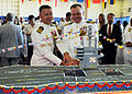 US Navy 100812-N-1004S-517 Capt. Thom W. Burke, left, and Capt. Kenneth J. Norton cut into a cake modeled after the aircraft carrier USS Ronald Reagan (CVN 76) during a reception following their change of command ceremony.jpg