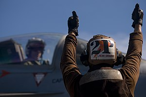 US Navy 120107-N-TZ605-223 Aviation Electrician's Mate Airman Seth Orourke, a plane captain assigned to Strike Fighter Squadron (VFA) 81, signals.jpg