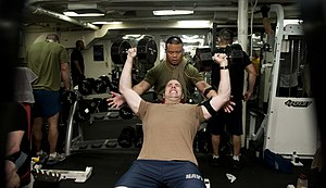 US Navy 120108-N-OY799-246 Lt. Cmdr. Kevin Gue, from Oakland, Calif., spots Lt. Todd Leroux, from San Diego, during a session of weightlifting aboa.jpg