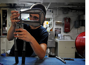 US Navy 120110-N-ZZ999-401 Airman Kaleb White adjusts a rivet squeezer while repairing a foreign object damage bucket.jpg